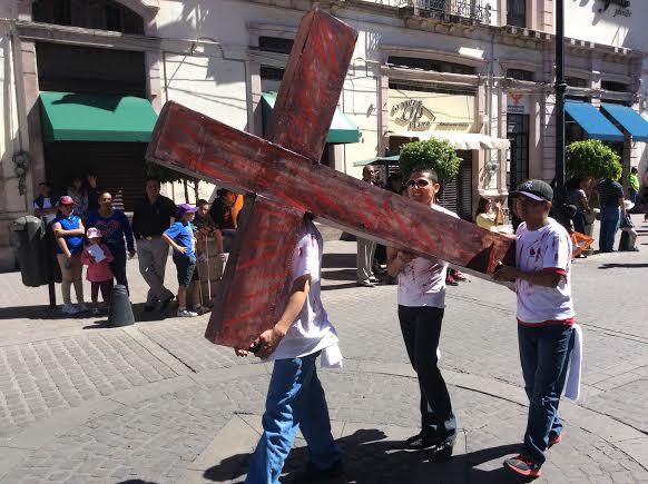 Cromistas protestan el día del obrero cargando una cruz